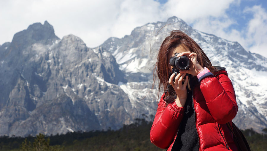 Woman photographing against mountain range