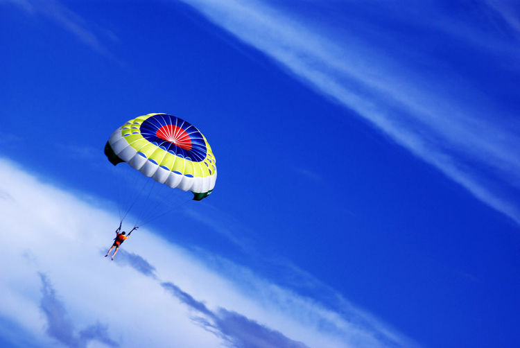 Low Angle View Of Man Parachuting Against Sky