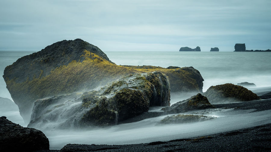 100ISO 50mm f/6.3 13s Sea Shore Rock Black Beach Iceland Beach Long Exposure Cliff Water Beauty In Nature Scenics - Nature Rock - Object Solid Sky Motion Land Rock Formation Nature No People Tranquility Day Tranquil Scene Idyllic Outdoors Horizon Over Water Power In Nature Stack Rock Flowing Water