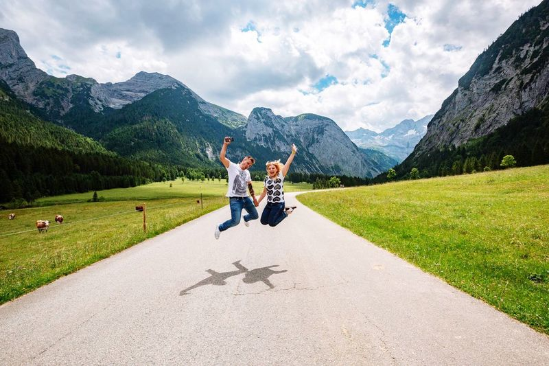 Happy couple jumping over road amidst mountains against sky