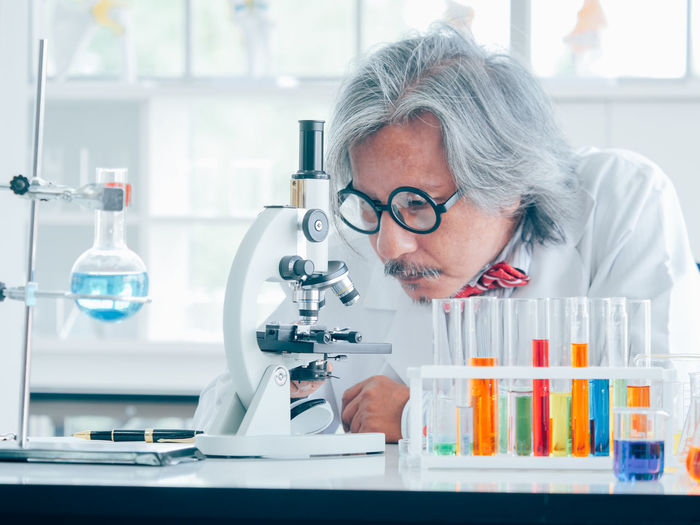 One Person Headshot Portrait Eyeglasses  Indoors  Healthcare And Medicine Front View Looking Adult Glasses Gray Hair Science Looking Down Real People Laboratory Equipment Research Concentration Laboratory Microscope Hairstyle Lab Coat