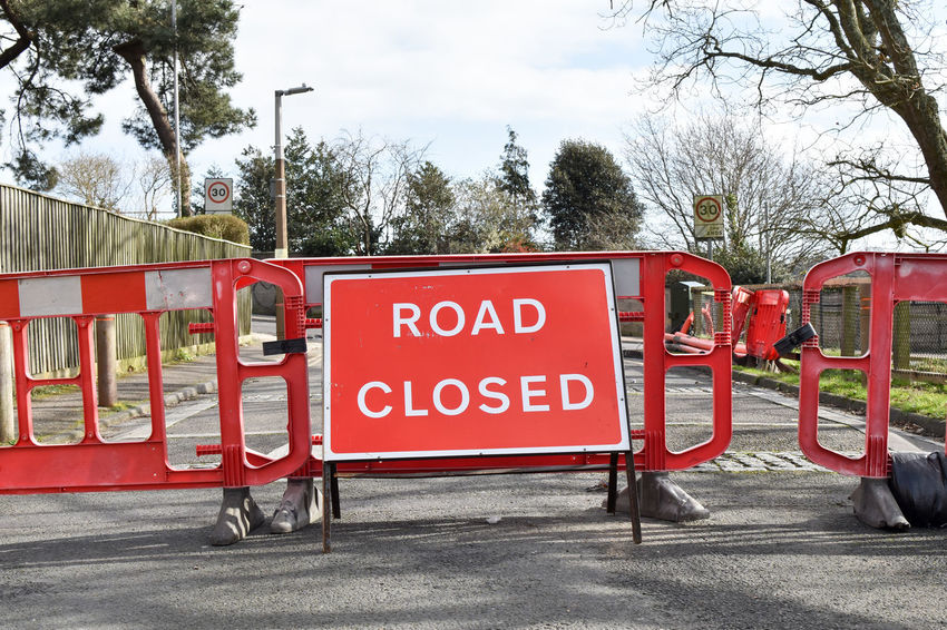 Road closed Road Construction Capital Letter City Communication Day Mode Of Transportation No People Outdoors Plant Red Road Road Closed Road Closed Sign Road Closure Road Sign Safety Sign Sky Street Text Transportation Tree Warning Sign