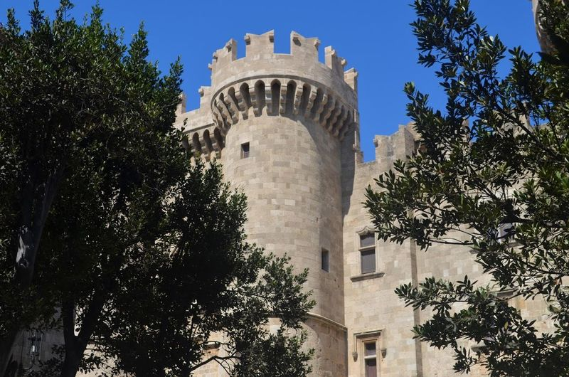 Architecture Blue Sky Built Structure Castle Culture Day Famous Place Fort Greece Historic Building History Medieval Outdoors Palace Of The Grand Masters Of The Nig Rhodes Tourism Tower Travel Destinations Tree