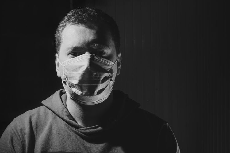 Close-up portrait of man with mask against black background