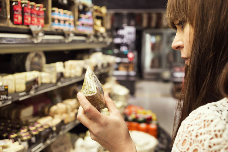 Midsection of woman holding ice cream in store