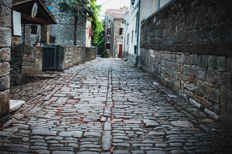 Surface level of cobblestone street amidst buildings