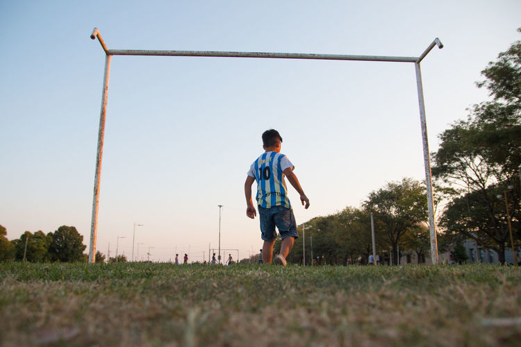 Rear view of boy on field against clear sky