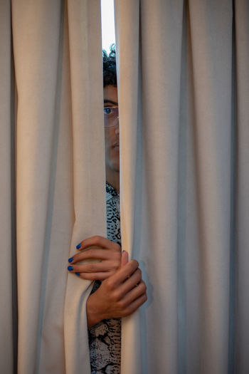Portrait of young man hiding behind curtain