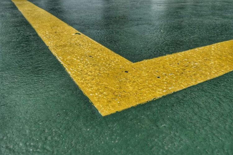 High angle view of yellow arrow symbol on wet road