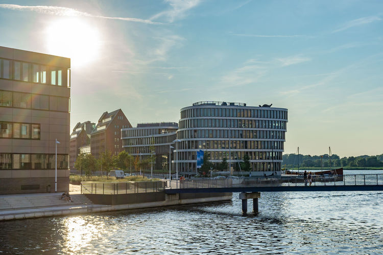 sunset in the city harbor of rostock Water Built Structure Architecture Building Exterior Sky No People Mode Of Transportation Cloud - Sky River Building Transportation City Sunlight Office Building Exterior Nautical Vessel Nature Waterfront Sun Day Outdoors Lens Flare Cityscape