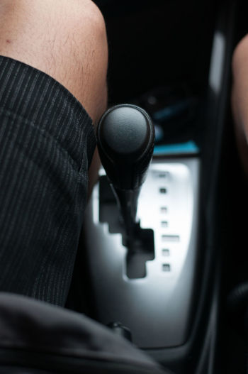 Cropped image of person sitting by gearshift in car