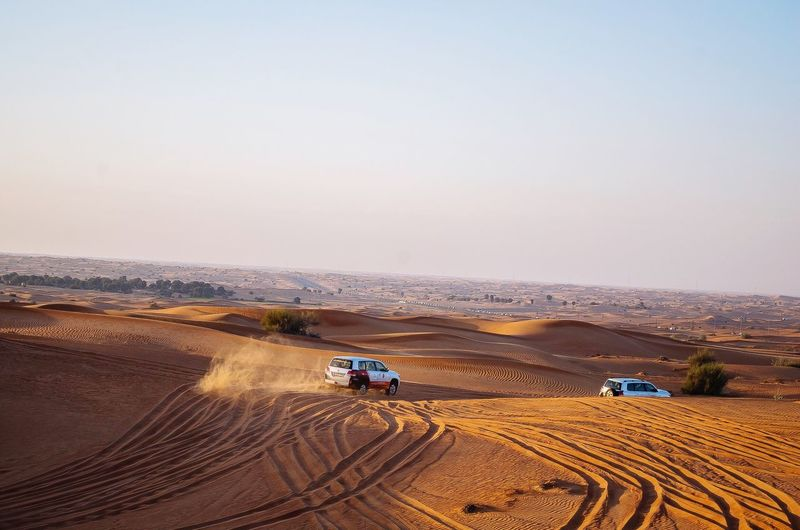 High Angle View Of Off-Road Vehicles At Desert Against Clear Sky