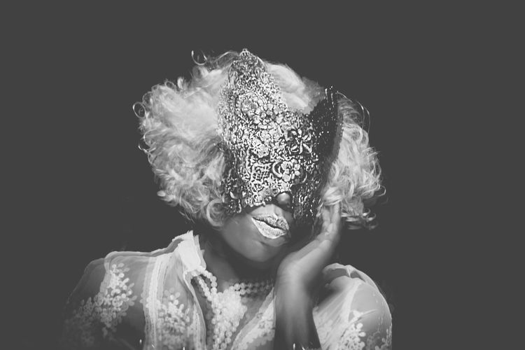 Woman Wearing Mask Against Black Background