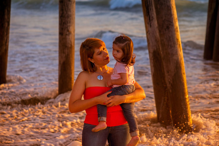 Young grandmother with her granddaughter by the ocean, enjoying some togetherness Casual Clothing Childhood Day Elementary Age Family Family Portrait Family Time FamilyTime Family❤ Focus On Foreground Girls Grandmother And Grandchild Hispanic Holding Latino Leisure Activity Lifestyles Love Minority Mother And Daughter Person Together Togetherness Tree Tree Trunk