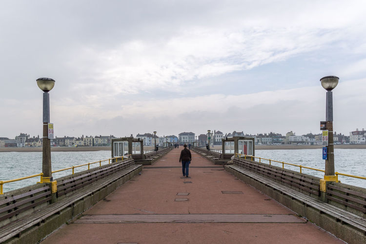 Rear View Of Person Walking On Pier Amidst Sea Against Sky