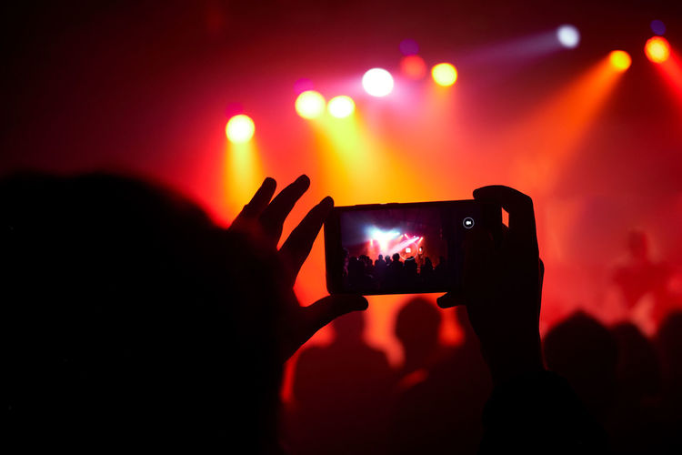 Activity Arts Culture And Entertainment Audience Communication Crowd Enjoyment Event Group Of People Hand Human Hand Illuminated Light Music Night Nightlife Performance Photographing Photography Themes Popular Music Concert Real People Smart Phone Stage Technology Wireless Technology Youth Culture