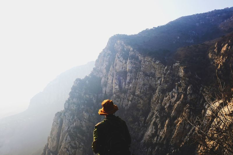 Rear view of person on rock by mountains against sky