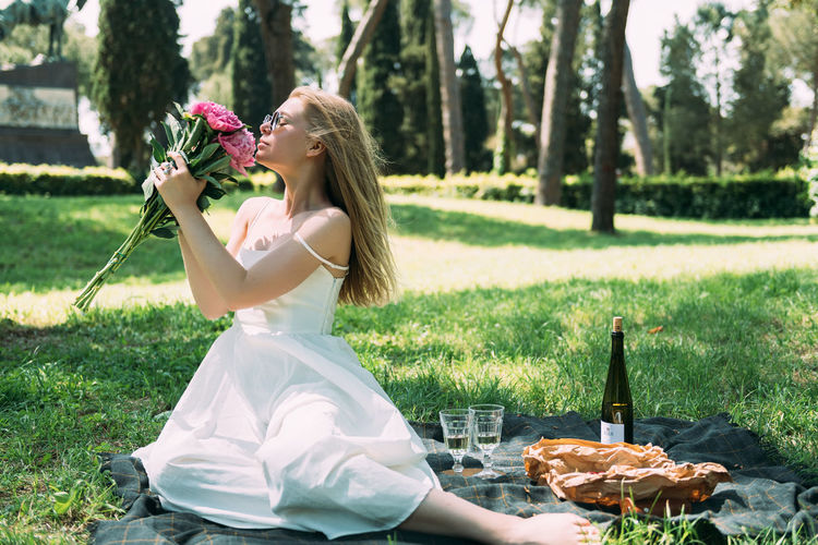 Woman with flowers sitting by wine bottle on picnic blanket