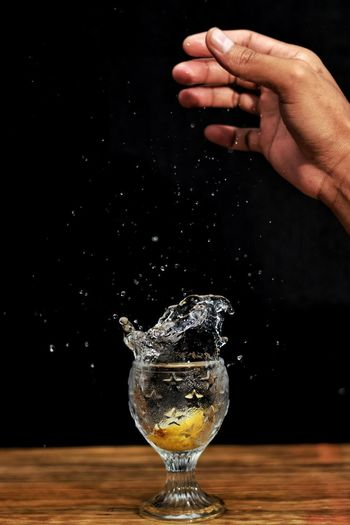 Close-up of hand pouring water in glass on table against black background