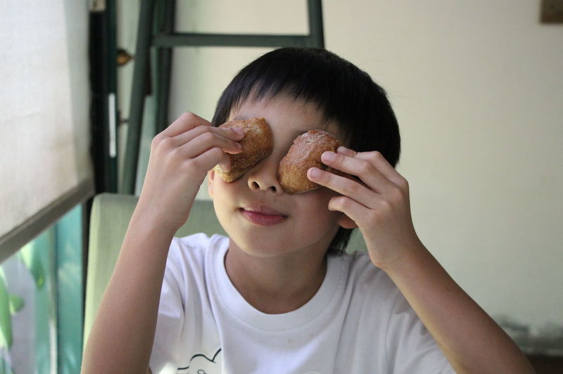 Close-Up Of Playful Boy Holding Food At Home