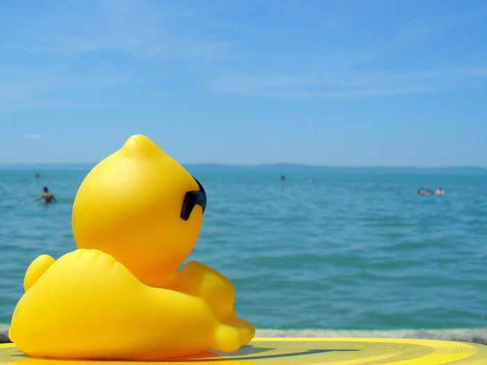 Yellow Rubber Duck By Sea Against Sky
