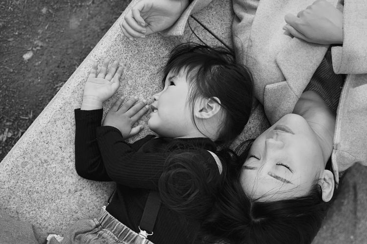 High angle view of siblings lying on floor
