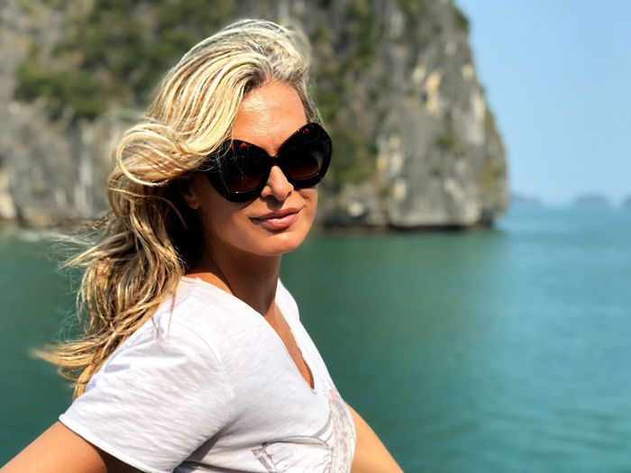 Portrait of woman wearing sunglasses against sea