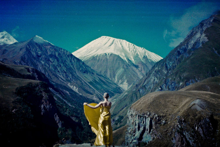 Rear view of bald woman wrapped in yellow textile while standing against mountains
