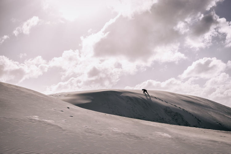 Silhouette Person Climbing On Sand Dunes Against Sky