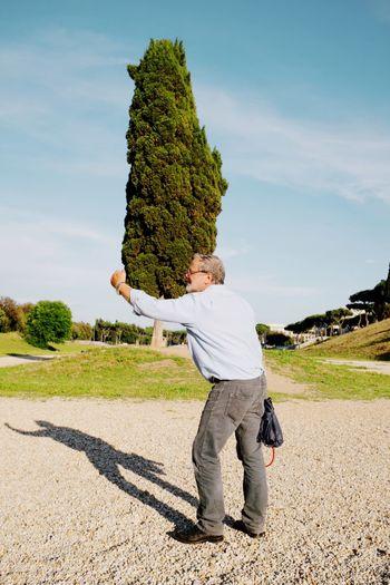 Optical illusion of senior man holding tree