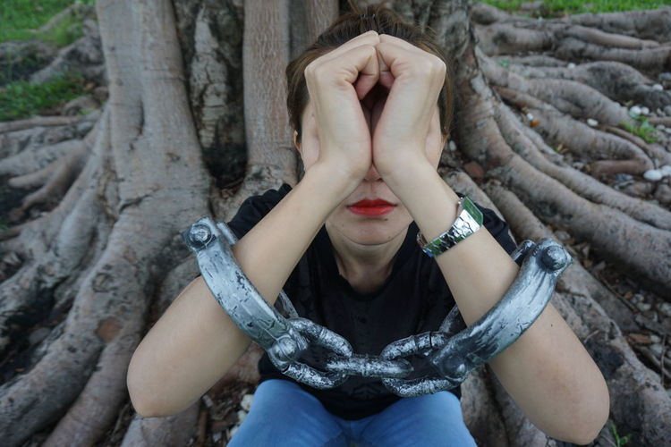 Low Section Of Woman Wearing Handcuffs While Sitting On Tree Trunk