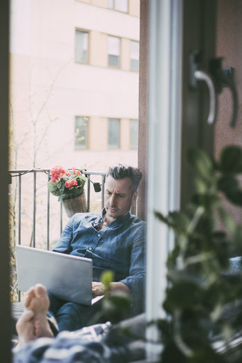 Man looking at camera while sitting by window