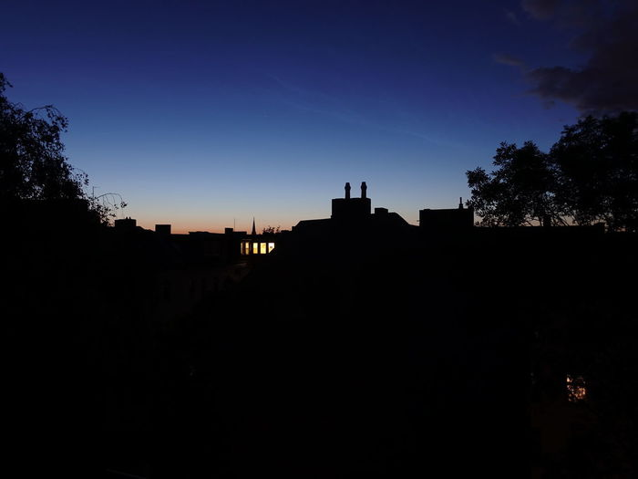 Silhouette buildings against clear sky at night