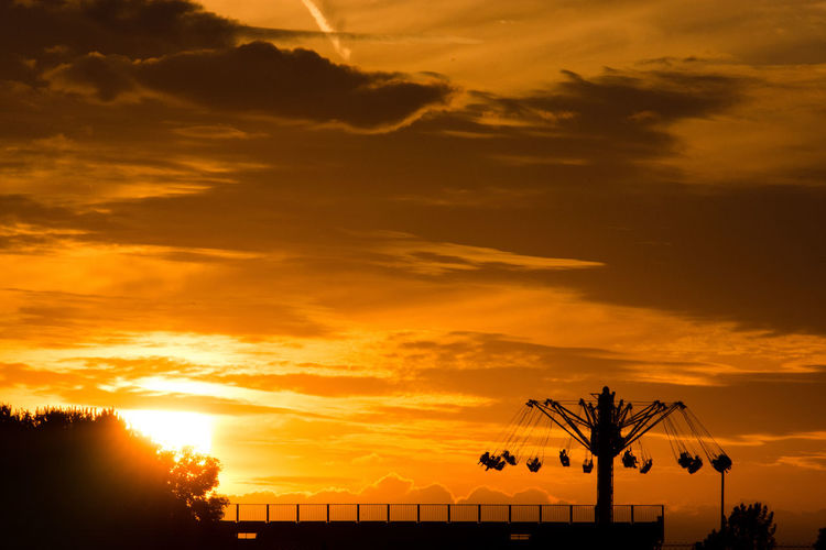 Silhouette Chain Swing Ride Against Cloudy Orange Sky During Sunset