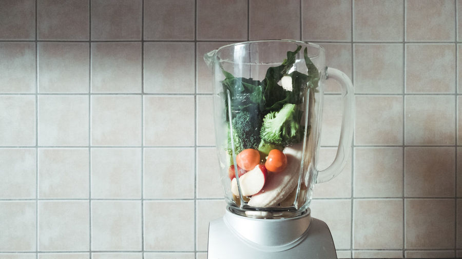 Close-up of vegetables and fruits in a mixer - making smoothies