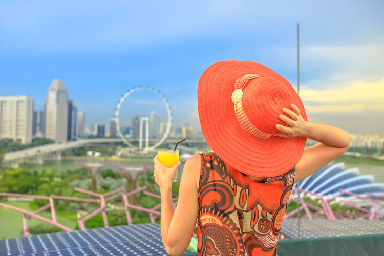 Lifestyle caucasian woman in wide hat drinking aperitif at rooftop cityscape skyline. Tourist enjoying above aerial view of Singapore marina. Travel holiday vacation in Singapore, Southeast Asia. Singapore Singapore City Woman Tourist Tourist Attraction  Tourist Destination People Girl Females Aerial View Skyline Cityscape Panorama Happy Travel Hat Lifestyle Enjoy Nature Tourism Aperitif Drink Orange Juice  Analcolic Glass One Person Sky Clothing Leisure Activity Real People Focus On Foreground Day Lifestyles Women Adult Architecture Rear View Cloud - Sky Sun Hat Built Structure Sitting Building Exterior Outdoors Looking At View