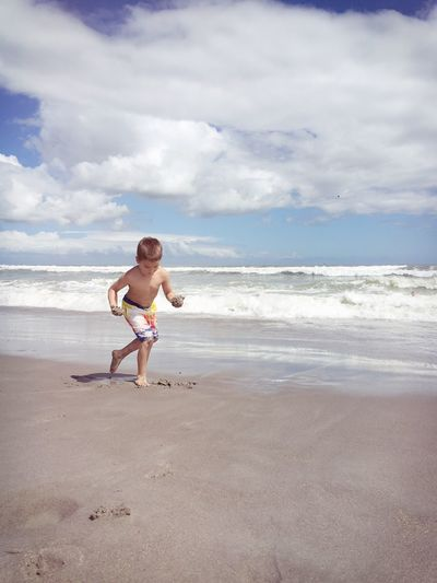 Shirtless boy playing on shore at beach against sky