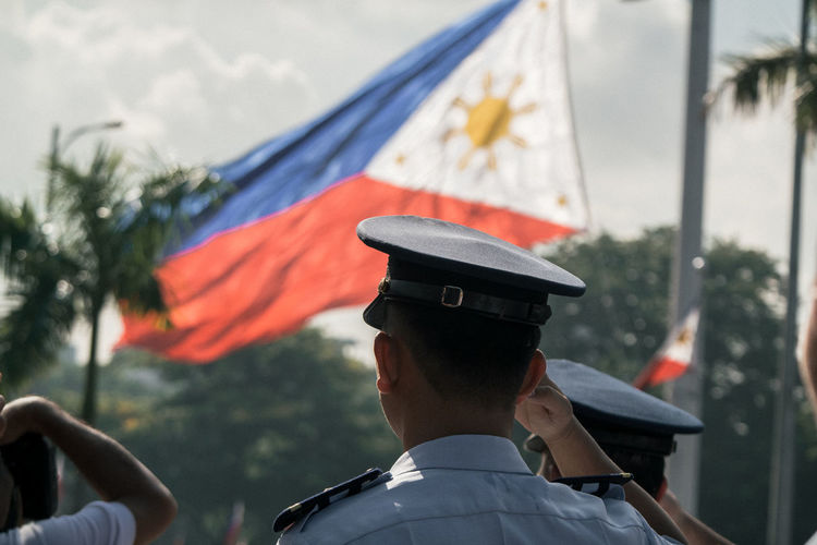 Rear view of police saluting philippines flag