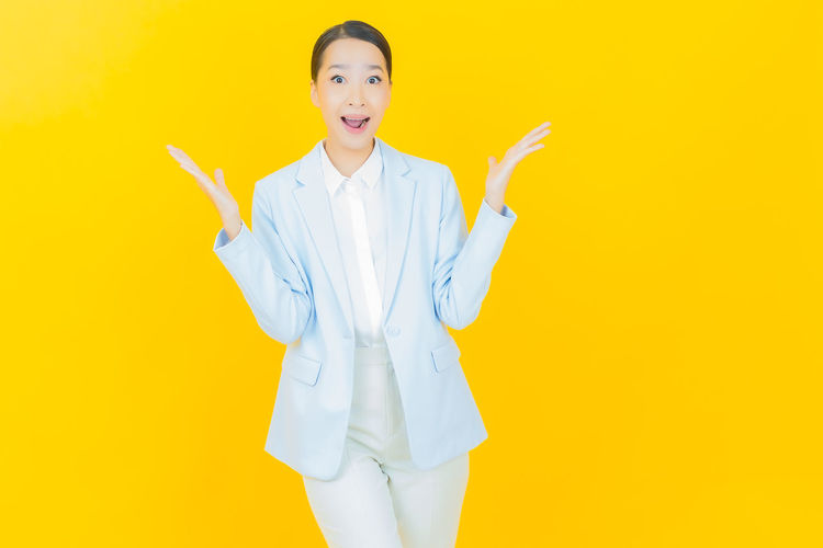 Portrait of a young woman standing against yellow background