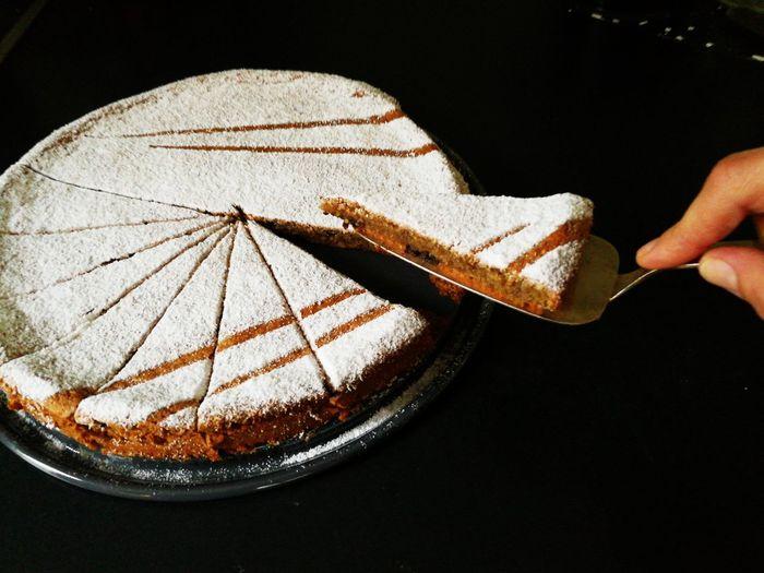 Ein Stück Kuchen zum Kaffee Tortenheber Nusskuchen Mandelkuchen Black Background One Person Close-up Human Body Part Indoors  Human Hand People