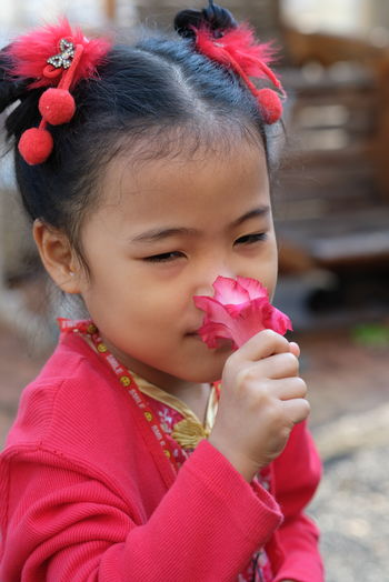 Close-up portrait of cute girl holding pink flower