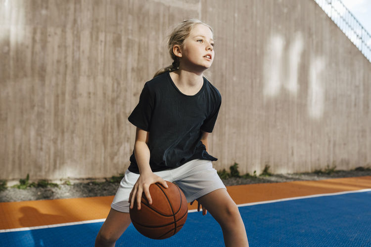 Full length of boy playing with ball against wall