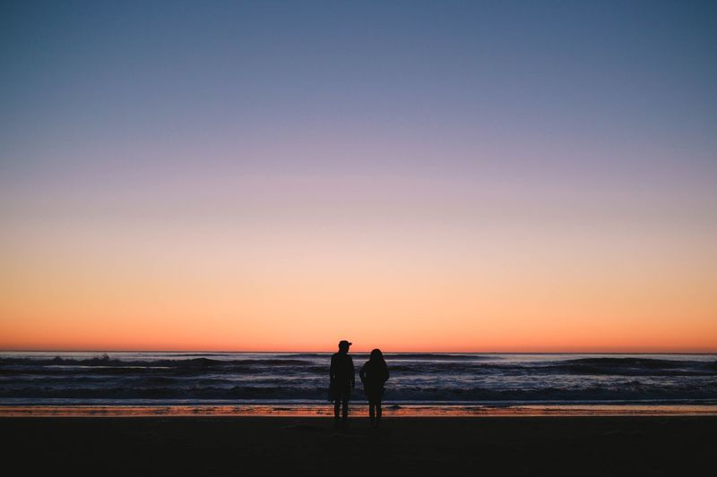 Silhouette couple standing on beach against clear sky during sunset