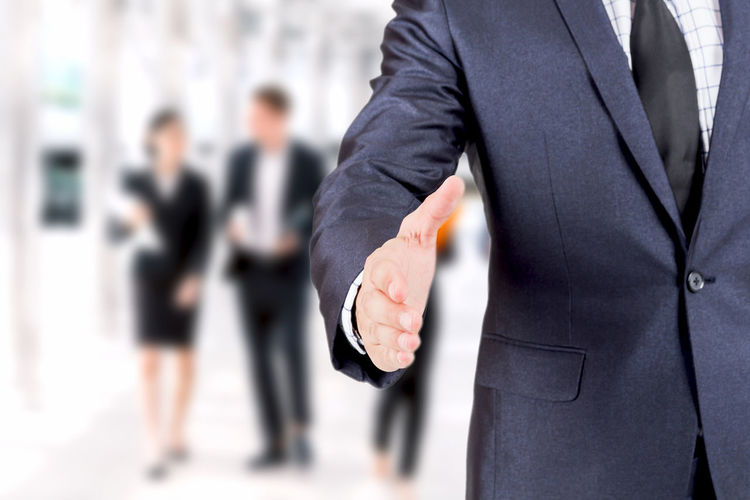Businessman offering handshake isolated on white background Adult Architecture Business Business Person Businessman Businesswoman Corporate Business Coworker Focus On Foreground Formalwear Full Suit Group Of People Hand Human Limb Males  Men Midsection People Standing Suit Well-dressed Women