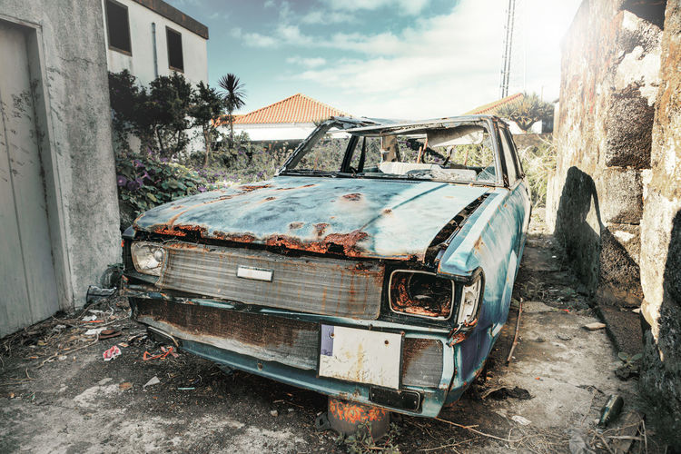 View of abandoned car against sky