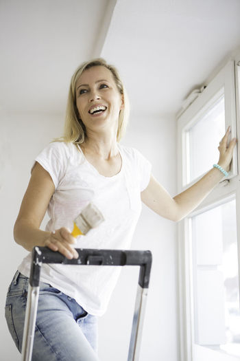 Young lady with a paint brush standing on a lady smiling Active Casual Clothing DIY Female Female Smiling Fun Jeans Ladder Leisure Activity Lifestyles Paintbrush Renovations Smile White Window Woman Smiling