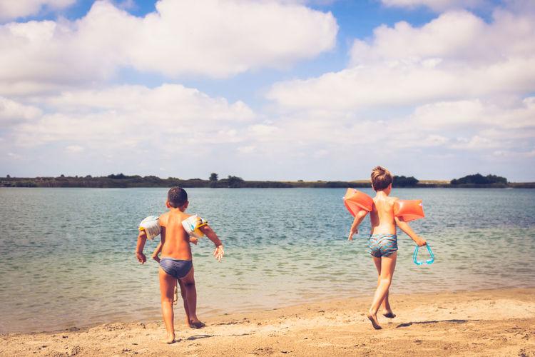 Full length of friends standing on beach against sky