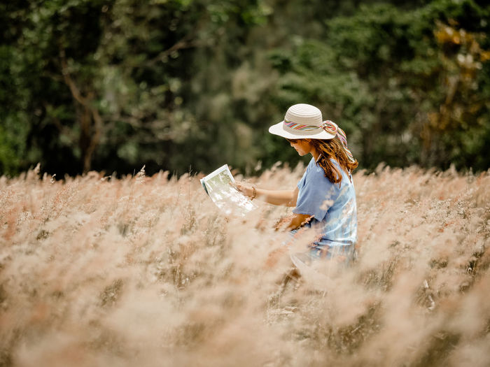 Woman wearing hat while reading map on field against trees
