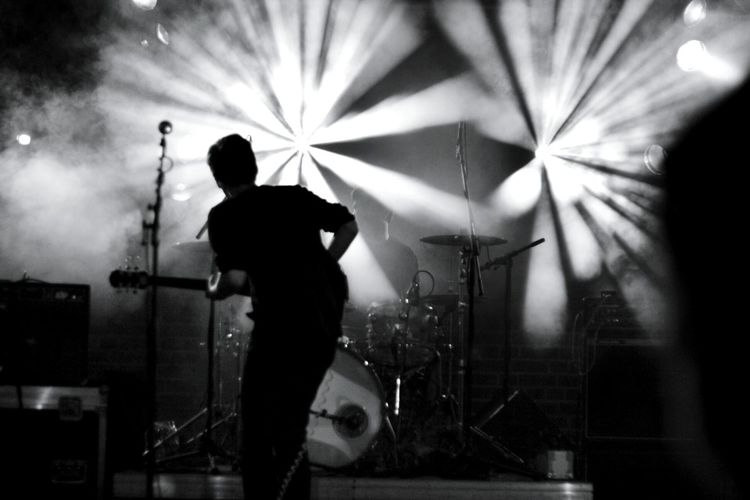 Rear view of man playing guitar at concert