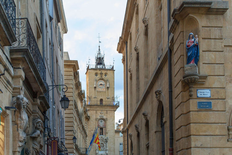 Building exterior at Aix-en-Provence, partial view of The City council Architecture Building Exterior Built Structure City City Life Clock Tower Cloud Commercial Sign Culture Day History Monument Old Town Outdoors Sky Statue Tall Tower Travel Destinations